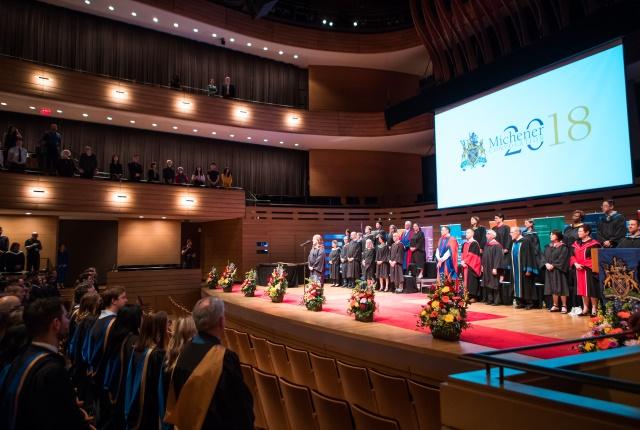 Graduates and platform party standing