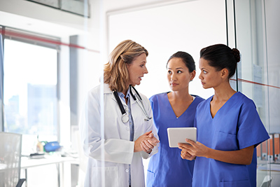 Shot of a female doctor giving two nurses their instruction