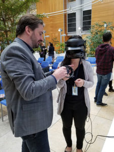 Jordan Holmes shows an individual how to use the virtual reality equipment