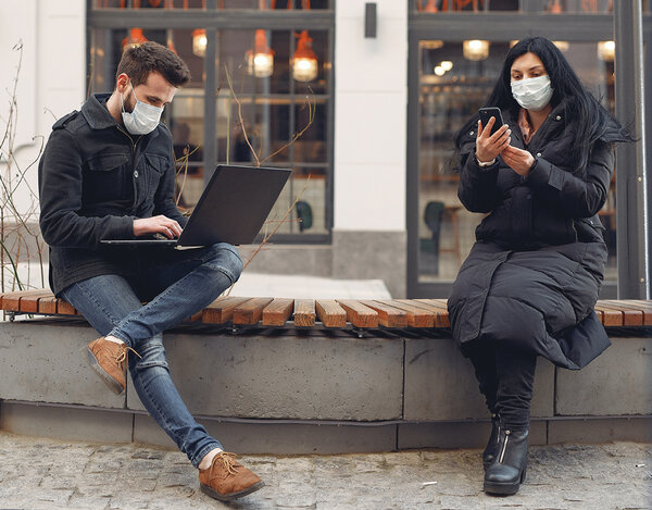 Two students in masks looking at their laptop and phone outside